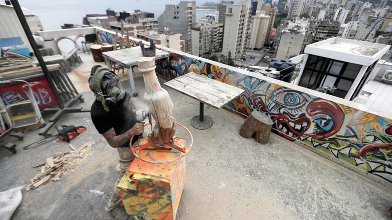 نحات ينفذ عمله الفني بالهواء الطلق.