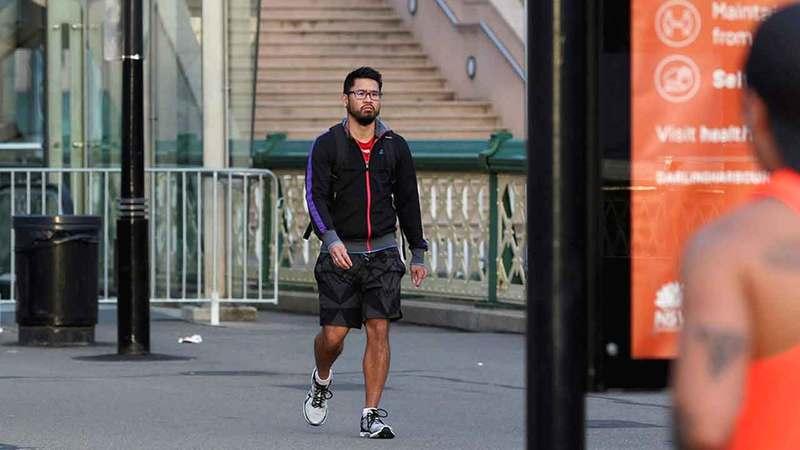 رجل يتريّض قبالة لافتة توعوية بأخطار فيروس كورونا بعد تخفيف القيود المفروضة على الحركة.  رويترز