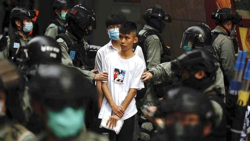 رجال الشرطة يعتقلون أحد المحتجين. أ.ب