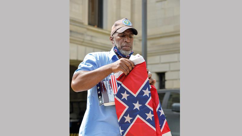 موظف يطوي العلم بعد إنزاله من على ساريته في مبنى كونغرس ولاية مسيسيبي. رويترز