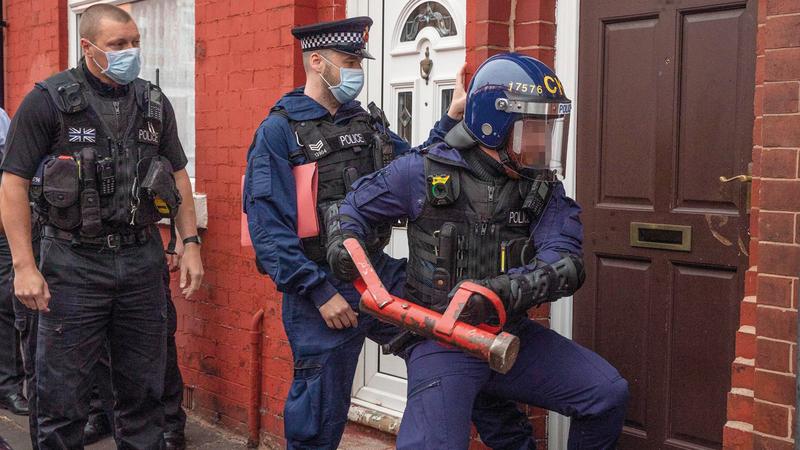 عناصر من الشرطة يقتحمون منزلاً بداخله مشتبه فيهم.  أرشيفية