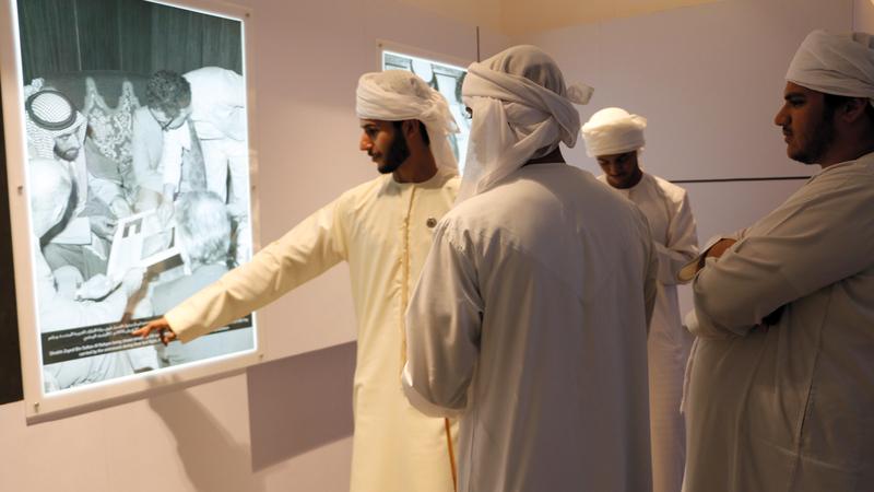 شباب من الإمارات يشاهدون صورة للشيخ زايد خلال استقباله وفداً من وكالة الفضاء الأميركية. «الأرشيف الوطني»