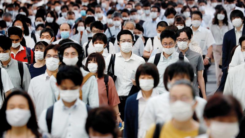 أشخاص يرتدون أقنعة واقية في محطة للسكك الحديدية بطوكيو.  رويترز