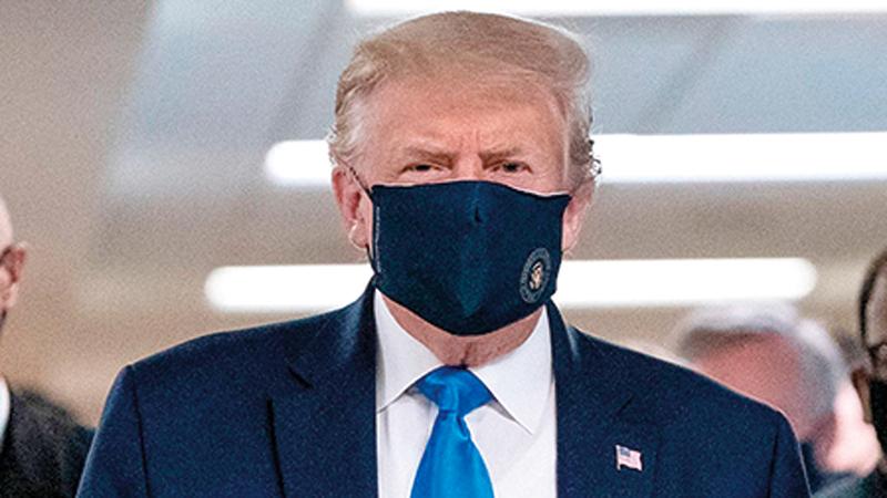 ترامب اضطر إلى ارتداء الكمامة بعد الزيادة الكبيرة في معدل الإصابات.   غيتي