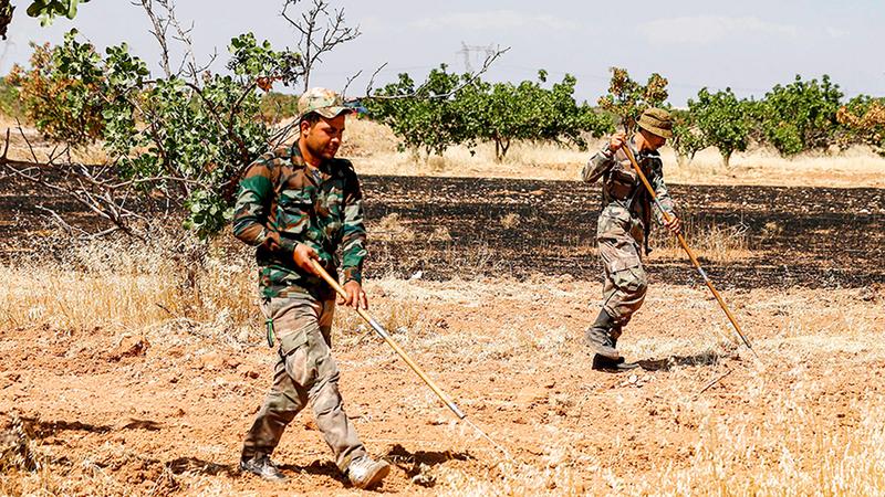 عناصر من الجيش السوري ينظفون أراضي البساتين من الألغام.■ أ.ف.ب