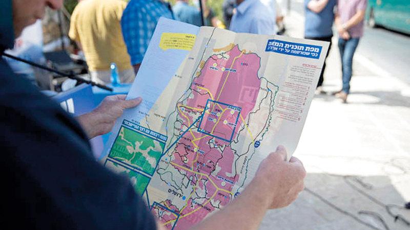 مستوطن إسرائيلي يحمل خريطة رسمت عليها مساحة الأراضي التي يسعى الاحتلال إلى ضمها.   أرشيفية