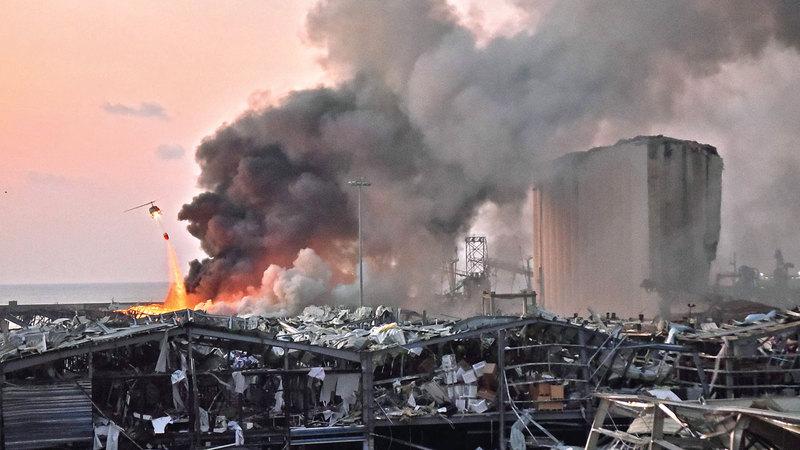 مروحية للجيش اللبناني تعمل على إخماد الحريق في المرفأ.  أ.ف.ب