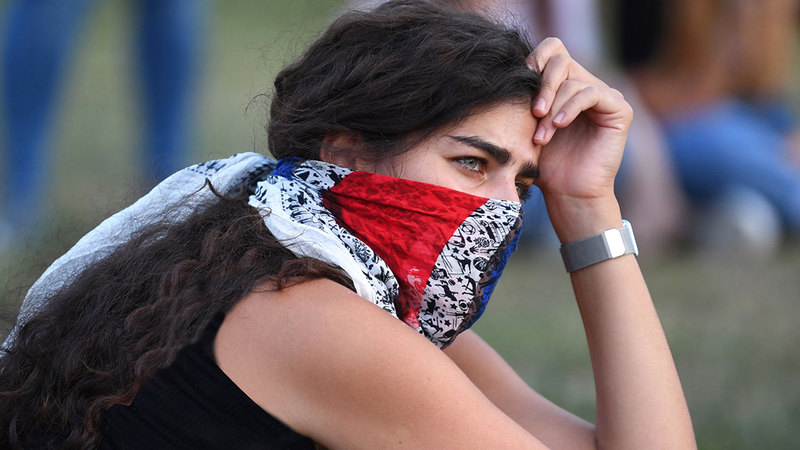ملامح الذهول تبدو واضحة على سيدة شاركت في فعالية حزناً على الضحايا في حديقة كينسينغتون بلندن.  إي.بي.إيه