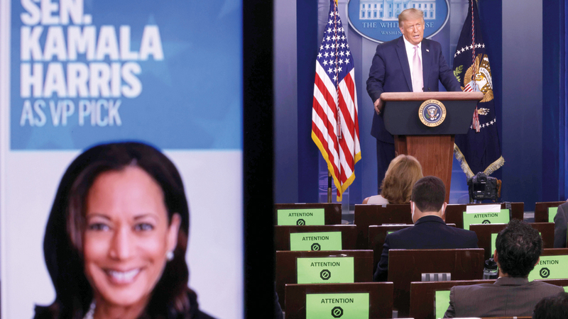 ترامب خلال مؤتمر صحافي.. وبجانبه صورة هاريس على شاشة كبيرة لحظة اختيارها نائبة لبايدن في حال فوزه بالرئاسة.  أ.ف.ب