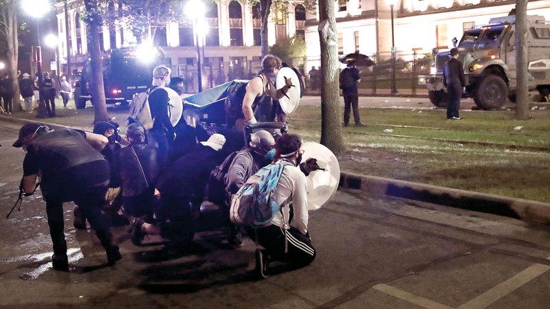محتجون يضعون السواتر لحماية أنفسهم خلال الصدامات.   أ.ف.ب