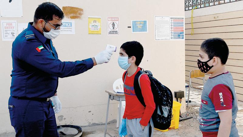 فحص درجة حرارة الطلبة قبل الدخول إلى المدرسة. تصوير: إريك أرازاس