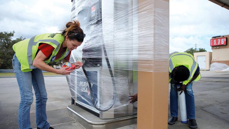 عاملان في محطة وقود يلفان المضخة بالنايلون حتى يحميانها من المواد التي ربما تحملها رياح الإعصار في المسيسبي. رويترز