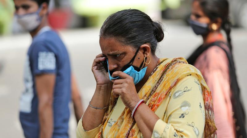 امرأة ترتدي أقنعة الوجه إجراء احترازياً ضد فيروس «كورونا» وتتحدث على الهاتف في مستشفى حكومي بجامو في الهند.  أ.ب