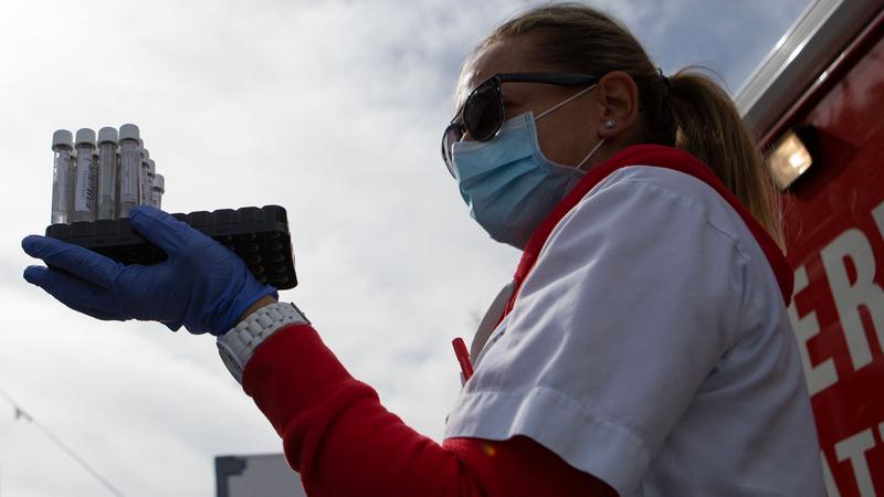 ممرضة تحمل عينات اختبار فيروس «كورونا» مأخوذة من المارة  في أحد شوارع فيينا.  أ.ف.ب