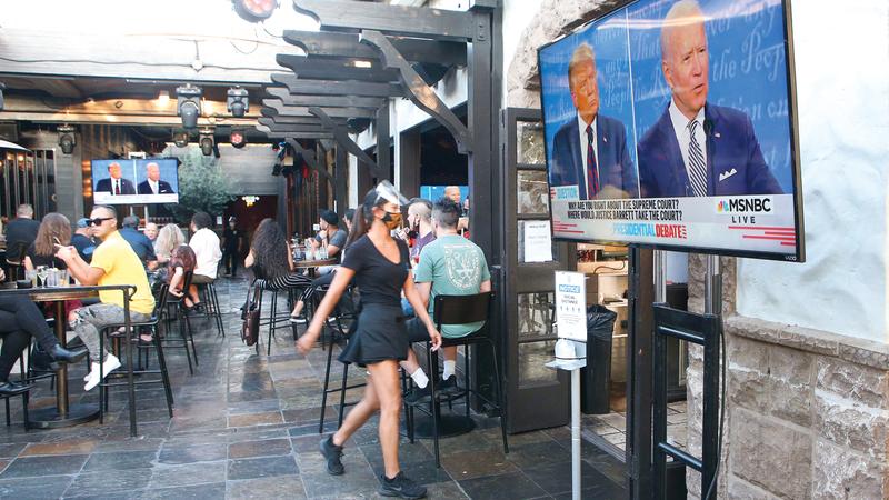 أميركيون يجلسون لمشاهدة المناظرة. أ.ف.ب