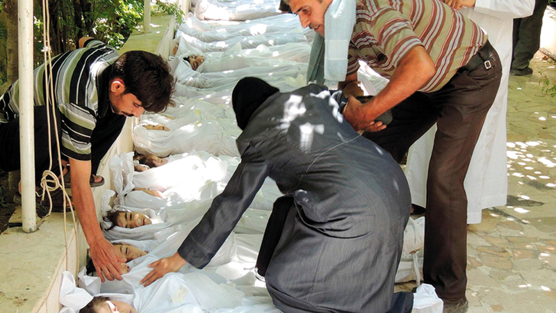 أم سورية تبحث عن أطفالها وسط الضحايا من الأطفال الذين تعرضوا لهجوم كيماوي في الغوطة. أ.ف.ب