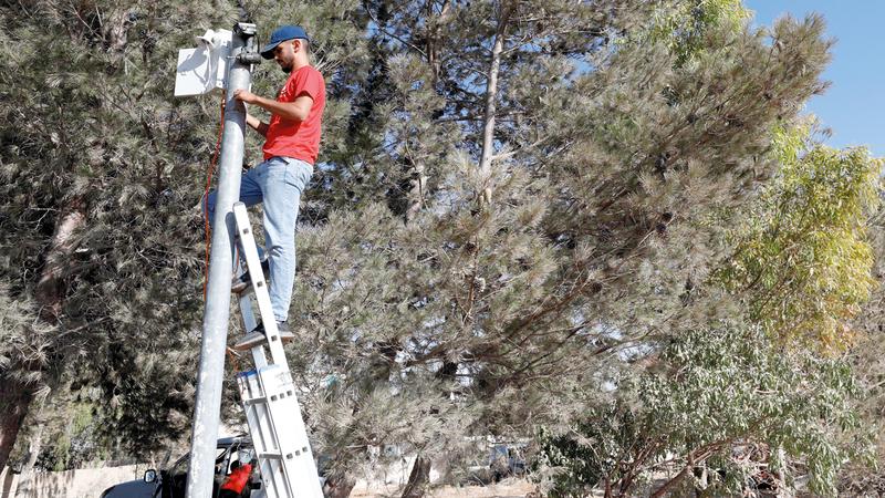 عامل يثبت كاميرا فيديو للمراقبة فوق عمود لتوثيق هجمات المستوطنين.  رويترز