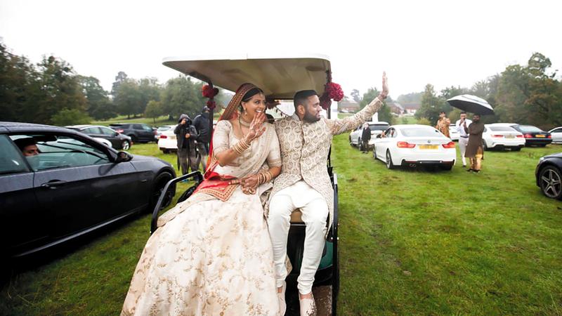 العريس وعروسه تجولا في عربة غولف وهما يلوحان للحضور.  أرشيفية