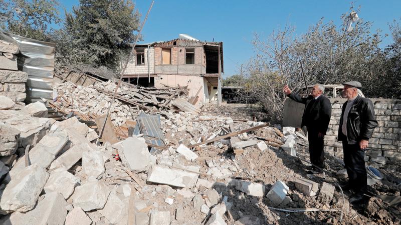 رجال يقفون بجوار أنقاض منزلهم المدمّر جراء المعارك في ناغورني قره باغ. رويترز