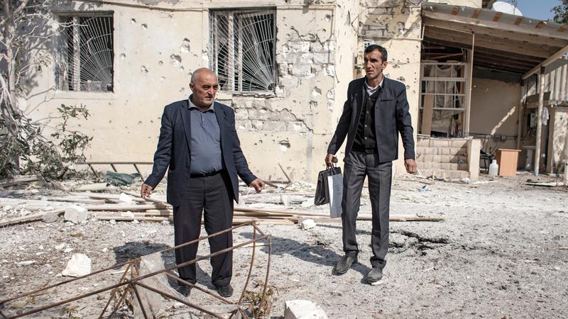 مواطنان يفحصان الدمار الذي لحق بالحي الذي يقطنان فيه في مدينة ترتر الأذرية إثر تعرضه للقصف.  أ.ب