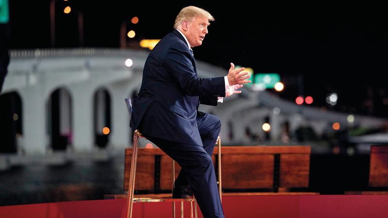 ترامب يجلس على كرسي خارج متحف بيريز للفن في ميامي. أ.ب