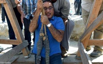 """الصورة: رئيس وزراء مصر يتدلى بحبل ليتفقد توابيت داخل """"بئر أثري"""""""