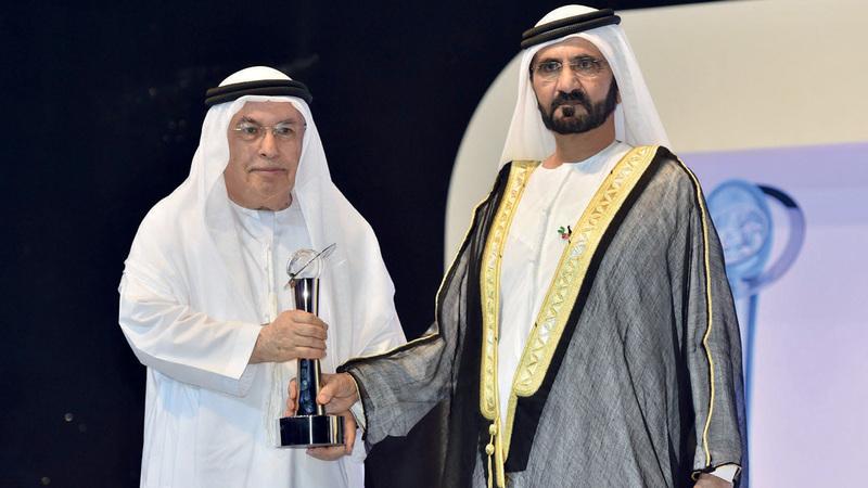محمد بن راشد خلال تكريم العابد بتسليمه جائزة شخصية العام الإعلامية عام 2014. أرشيفية