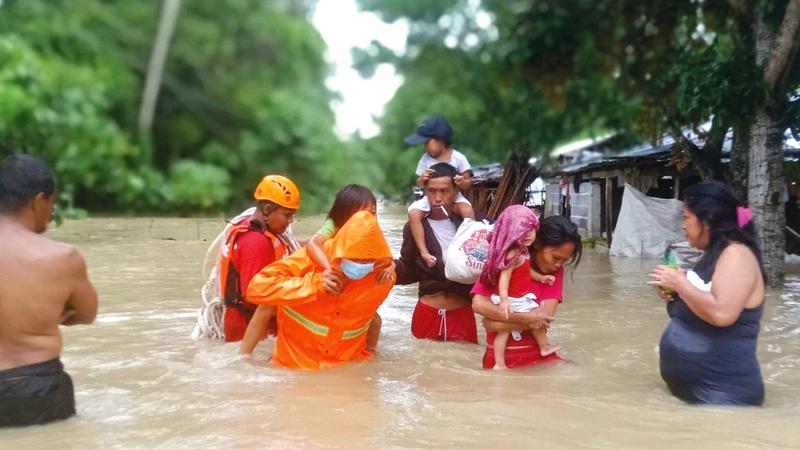 منقذون يحملون الأطفال لإجلائهم إلى مناطق آمنة بعيداً عن خطر الفيضان.   إي.بي.إيه