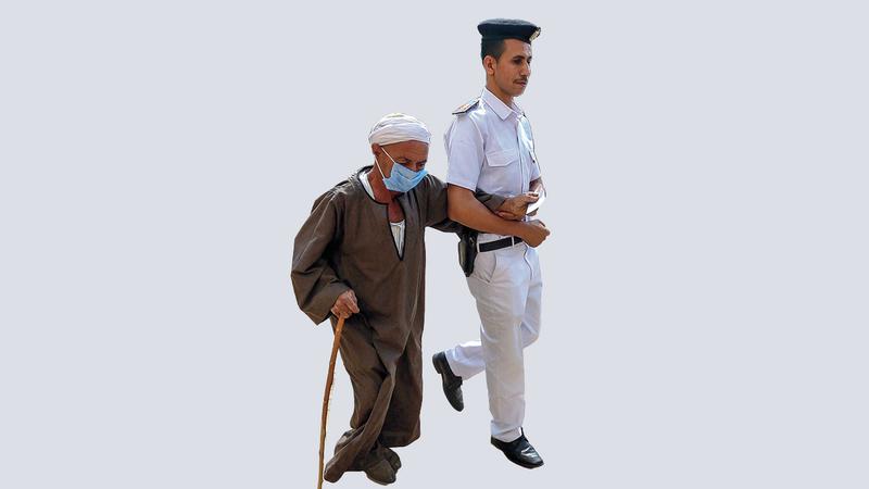شرطي يقود عجوزاً للإدلاء بصوته. أ.ف.ب
