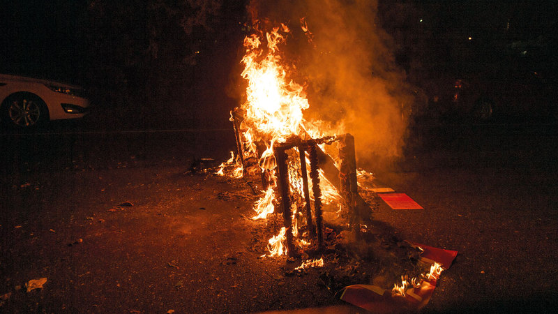 ألسنة اللهب تتصاعد بعد أن أشعل المتظاهرون النيران في الشوارع.   أ.ب