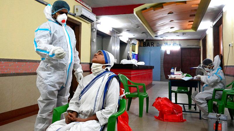 ممرض هندي يجري اختبار مسحة على راهبة في عيادة متنقلة لاختبار «كورونا» في كولكاتا.  أ.ف.ب