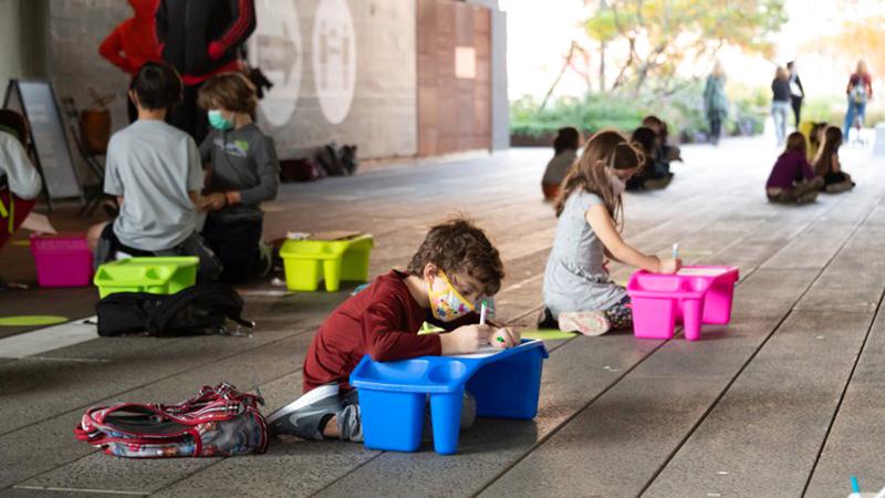 طلبة بمدرسة في نيويورك سيتي يؤدون واجباتهم المدرسية خارج الفصول خوفاً من الإصابة بـ«كورونا». غيتي