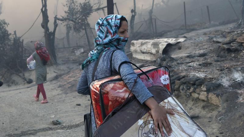 لاجئة تحمل متعلقاتها بعد أن شبّ حريق بمخيم لاجئين بجزيرة ليسبوس اليونانية في سبتمبر 2020.  رويترز