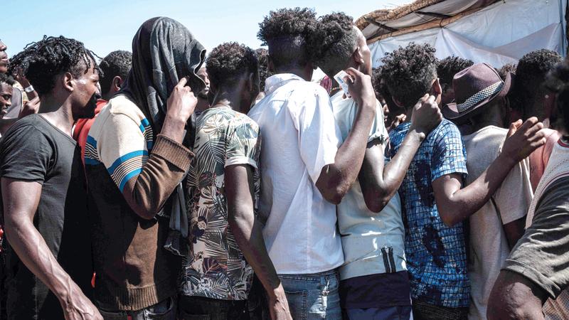 لاجئون من إثيوبيا وصلوا السودان يصطفون للتسجيل لتلقي إمدادات الطعام.   أ.ف.ب