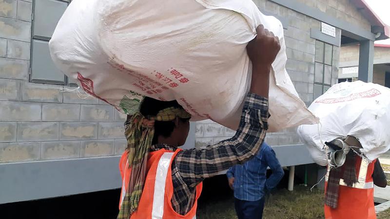 حمّال يحمل أمتعة أحد اللاجئين الروهينغا في بيسان شار.   أ.ب