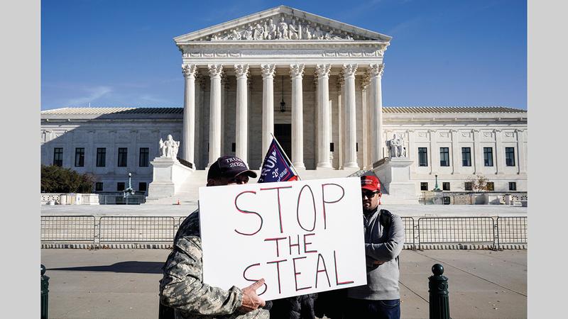 أنصار ترامب خارج المحكمة العليا وأحدهم يرفع لافتة تزعم «سرقة الانتخابات». رويترز