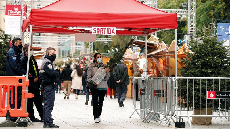حارس أمني ينظم دخول المتسوقين إلى سوق الكريسماس في سانت لوسيا بإسبانيا.   رويترز