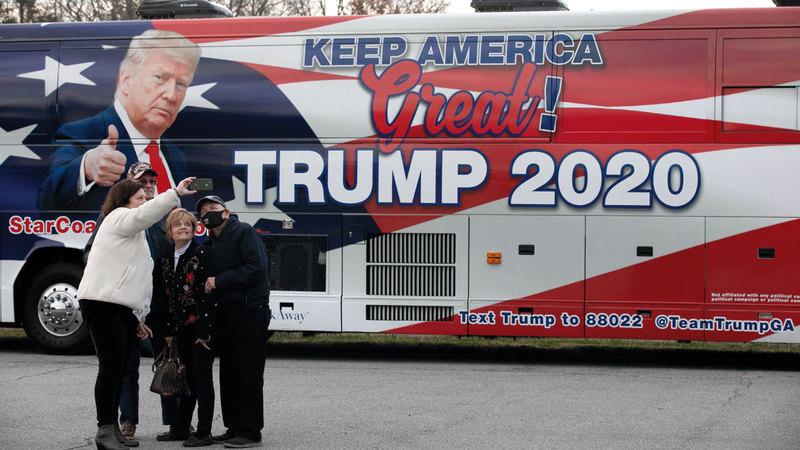 أنصار لترامب يلتقطون صوراً بجوار حافلة تحمل شعارات حملته الانتخابية في جورجيا.   أ.ف.ب