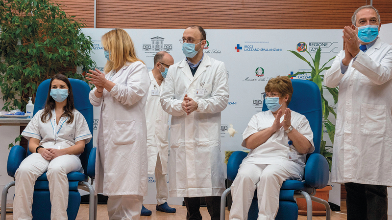 عاملون في الرعاية الصحية بروما يصفقون مع انطلاق حملة التطعيم. إي.بي.إيه