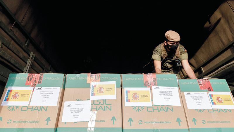 جندي إسباني يفرّغ صناديق مملوءة بلقاحات مضادة لـ«كورونا». إي.بي.إيه