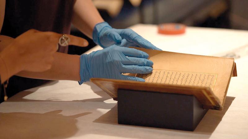 فريق فني متخصص يتعامل مع المخطوطات النادرة في القصر.  من المصدر
