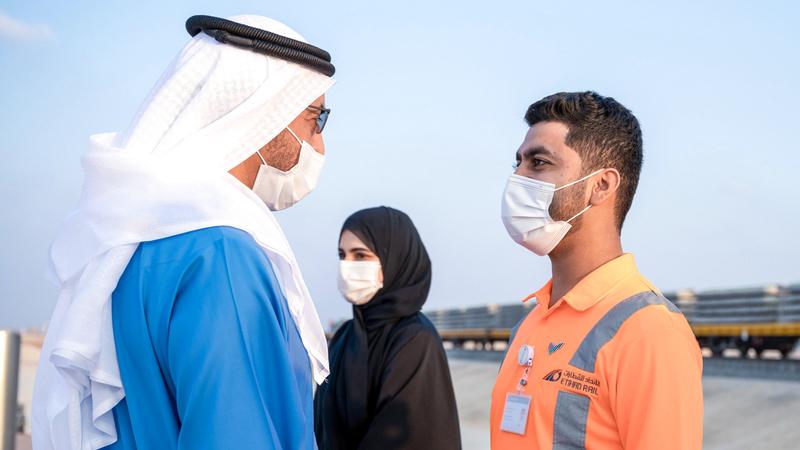 حمدان بن زايد خلال حديث مع أحد المواطنين العاملين في المشروع. وام
