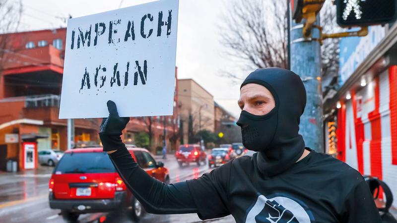 أحد المتظاهرين على سلوك ترامب يرفع لافتة تنادي بمساءلته مرة أخرى وعزله.إي.بي.إيه