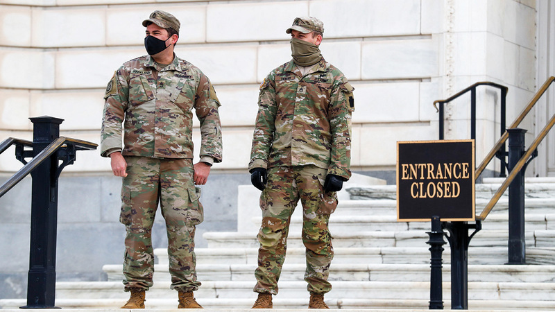اثنان من عناصر الجيش الوطني يقفان عند أحد مداخل الكونغرس ضمن إجراءات تعزيز الأمن حول مبنى «الكابيتول». إي.بي.أيه
