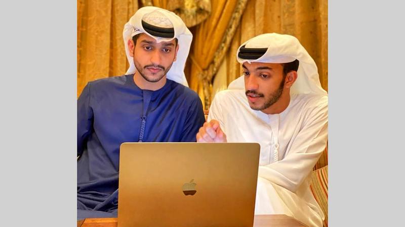 راشد محمد (يسار) يساعد أحد أصدقائه في إعداد قائمة طعام رقمية.  من المصدر