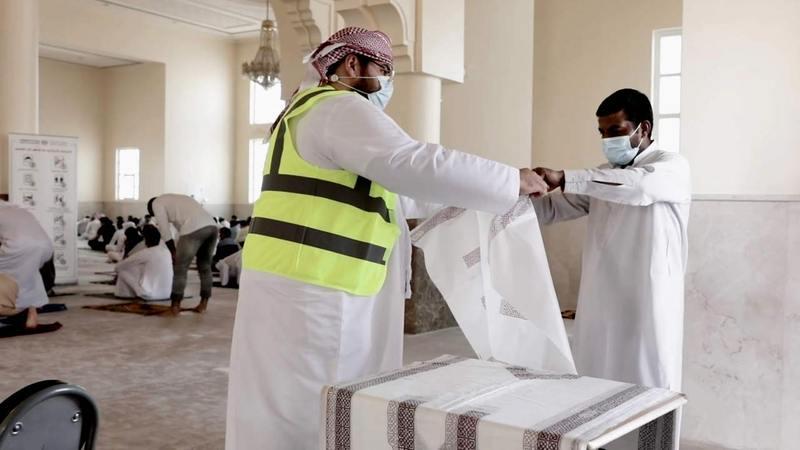 متطوعون يوزعون سجادات صلاة بلاستيكية على المصلين. من المصدر