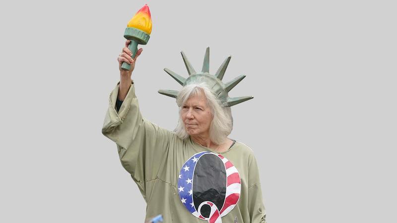 امرأة تتقمص شخصية تمثال الحرية ترتدي قميص حركة كيو أنون خلال تظاهرة في كولمبيا في السادس من يناير 2021.  أ.ب