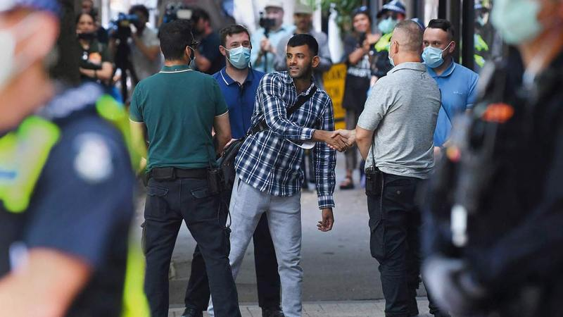 أحد اللاجئين المحتجزين في الفندق يصافح أحد الحراس بعد إطلاق سراحه.   إي.بي.إيه