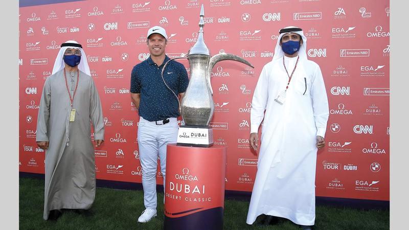 نجم الغولف الإنجليزي كايسي يتوسط الشيباني وبن سليم خلال مراسم التتويج.  من المصدر