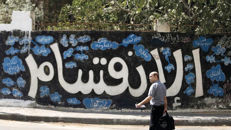 لوحة جدارية تظهر آثار وويلات الانقسام في الفلسطينيين.  أ.ف.ب